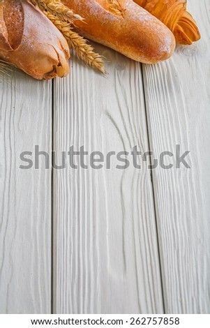 copyspace image baguettes and ears of wheat rye on vintage wooden painted boards food and drink concept - stock photo