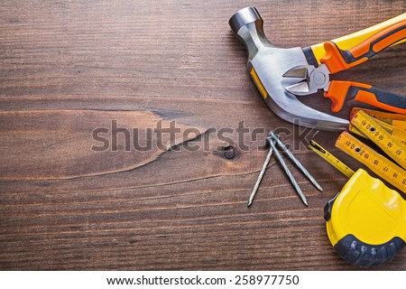 copyspace image claw hammer nails tapeline wooden meter nippers on vintage board construction concept  - stock photo