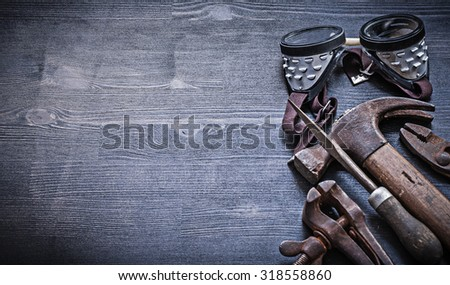 copyspace image goggles rasp hammer pliers on vintage wood board. - stock photo