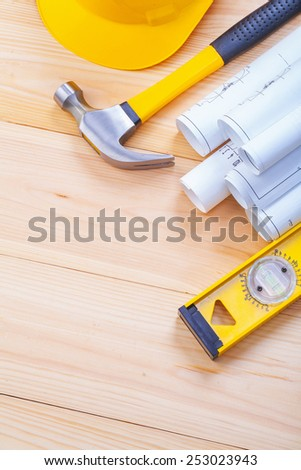 copyspace image set of tools construction level stack rolld blueprints claw hammer helmet on wooden boards