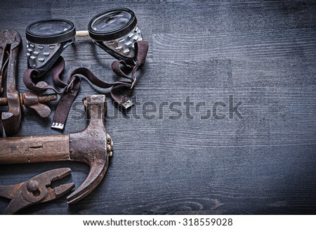 copyspace view goggles hammer pliers on vintage wood board. - stock photo