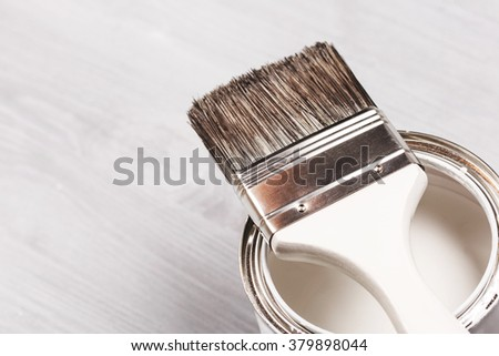Copyspace with paintbrush and can with white paint lying on white wooden clean table. Top view. Copy space. - stock photo