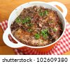 Coq au vin, chicken casseroled in red wine. - stock photo