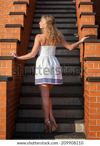 Coquettish young beautiful woman posing near the stairs at sunset - stock photo