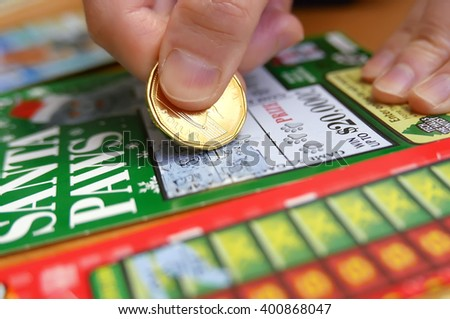 Coquitlam BC Canada - January 24, 2015 : Woman scratching lottery tickets. The British Columbia Lottery Corporation has provided government sanctioned lottery games in British Columbia since 1985.