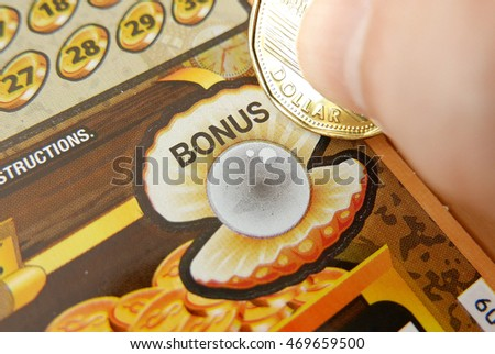 Coquitlam BC Canada - June 04, 2015 : Woman scratching lottery ticket on bonus section. The British Columbia Lottery Corporation has provided government sanctioned lottery games in BC since 1985.