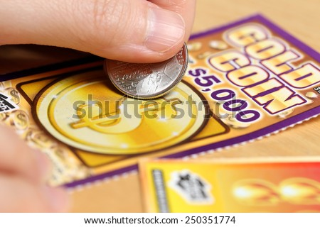 Coquitlam BC Canada - June 15, 2014 : Woman scratching lottery tickets. The British Columbia Lottery Corporation has provided government sanctioned lottery games in British Columbia since 1985.  - stock photo