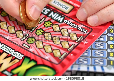 Coquitlam BC Canada - March 26, 2014 : Scratching lottery tickets. The British Columbia Lottery Corporation has provided government sanctioned lottery games in British Columbia since 1985.  - stock photo