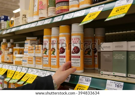 Coquitlam, BC, Canada - October 08, 2015 : Woman selecting nature's burt's bees shampoo in grocery store  - stock photo