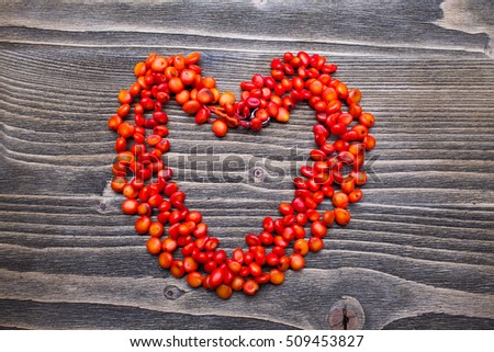 coral beads in the shape of heart on a wooden background
