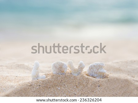 coral letters spelling the word love on the beach in hawaii - stock photo