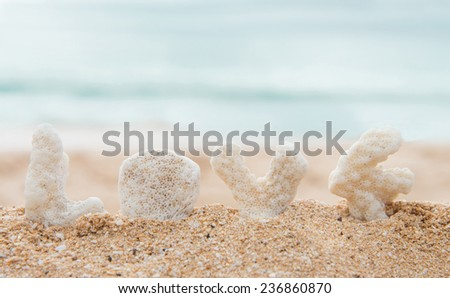 """Coral letters spelling the word """"love"""" with the ocean in the background  - stock photo"""