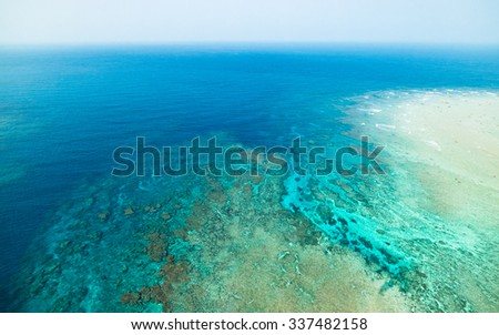 Coral reef and clear blue tropical sea from above by paragliding flight, Amami Oshima Island, Kagoshima, Japan