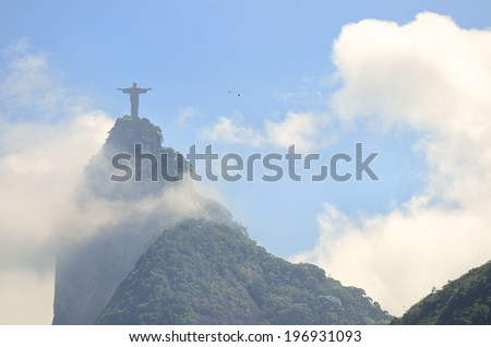 Corcovado mountain Christ the Redeemer standing above swirling mist clouds and jungle in Rio de Janeiro Brazil