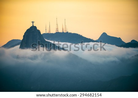 Corcovado mountain Christ the Redeemer standing in golden sunset above swirling mist clouds Rio de Janeiro Brazil - stock photo