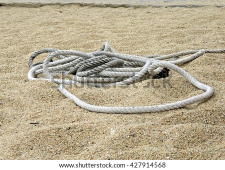 Cord of a fishing boat in the sand on a beach - stock photo