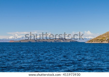 Cordillera Real mountain range behind Titicaca lake, Bolivia. Isla de la Luna also visible. - stock photo