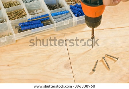 cordless drill, screws and toolbox on a wood background - stock photo