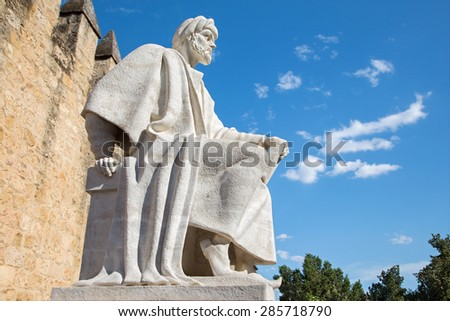CORDOBA, SPAIN - MAY 25, 2015: The statue of medieval arabic philosopher Averroes by Pablo Yusti Conejo (1967) and the medieval walls.