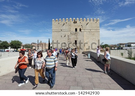 CORDOBA, SPAIN - MAY 10: Tourists on the ancient roman bridge during the Festival of the Patios on May 10, 2013 in Cordoba, Andalusia Spain.