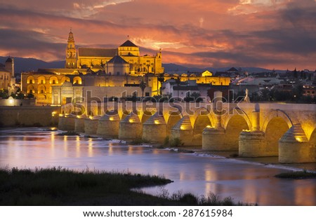Cordoba - The Roman bridge and the Cathedral in the background at dusk - stock photo