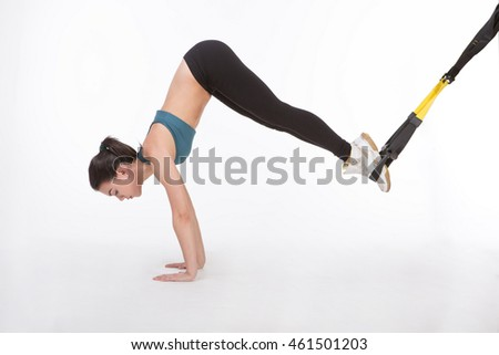 Core body exercise concept. Beautiful lady training with suspension trainer sling. Young attractive woman doing suspension training with fitness straps in studio.