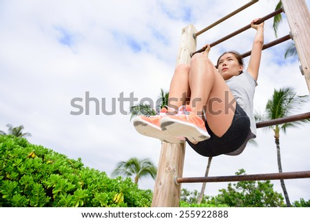 Core cross training fit woman doing abs exercises on beach on fitness vertical ladder rack. Young active athlete working out abs muscles outside. - stock photo