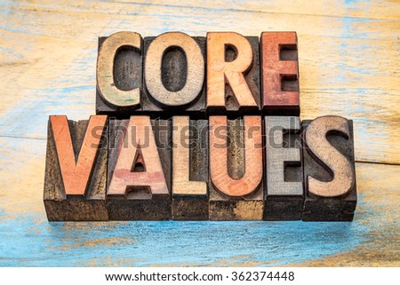 core values  banner  - text in vintage letterpress wood type blocks stained by color inks against grunge wood - stock photo