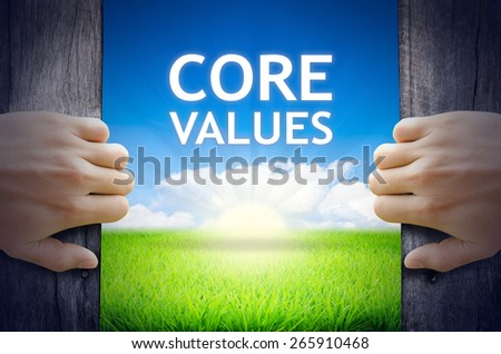 Core Values. Hands opening a wooden door then found a texts floating among new world as green grass field, Blue sky and the Sunrise. - stock photo