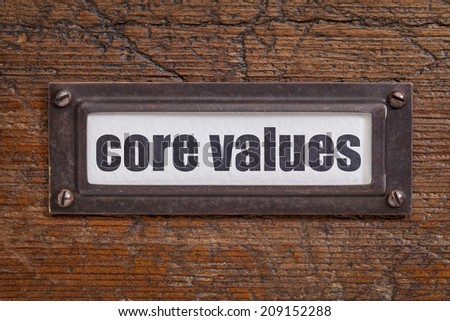 core values tag - file cabinet label, bronze holder against grunge and scratched wood