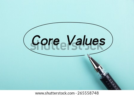 Core values text is on blue paper with black ball-point pen aside. - stock photo