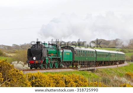 CORFE, UK - APRIL 17: Vintage steam train Cheltenham heads a passenger train of visitors towards Norden station during the Swanage Railway spring steam gala on April 17, 2015 in Corfe.