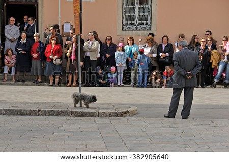 CORFU, GREECE - APRIL 18, 2009: A police officer in civilian clothes looks at a dog urinating on a pole, while onlookers anticipate a reaction.