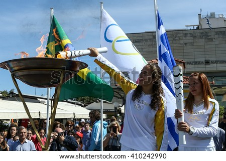 Corfu, Greece - April 22, 2016: Athletes carrying the Olympic Flame on the Torch Relay leg for the Rio 2016, from city to city in Greece  - stock photo