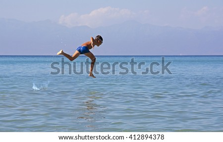 Corfu, Greece - June 29, 2014: A young unidentified boy running through the sea. Perfect background for a text