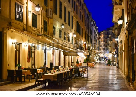 Corfu old town (Kerkyra) city streets at night with restaurants and pedestrain paved roads - stock photo