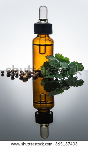 Coriander essential oil bottle (open) with dropper, coriander leaves and seeds
