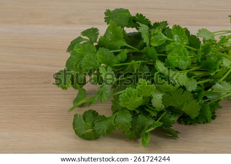 coriander leaves heap on the wooden background - stock photo