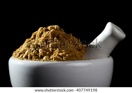 Coriander Powder with mortar and pestle on black background. - stock photo