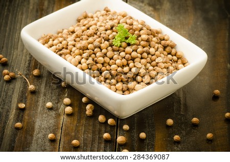 Coriander seed in the bowl on wooden background