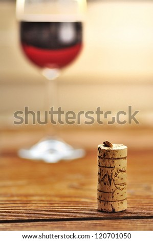 Cork and glass of italian red wine on a table in oak, closeup, selective focus - stock photo