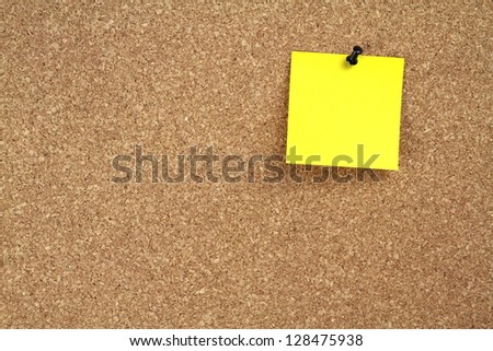 Cork board and yellow note paper - stock photo