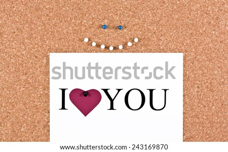 Cork board cheerful smiley face and a sheet with the words I love you - stock photo
