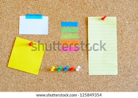 Cork board with multiple colorful objects on it - stock photo