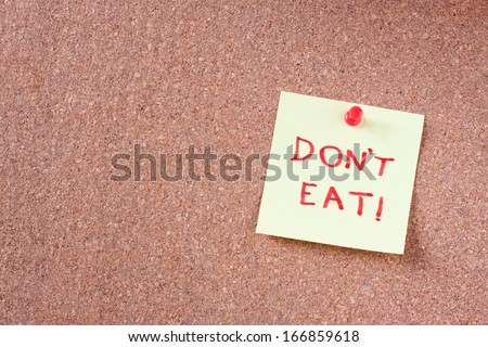 "cork board with pinned yellow note and the phrase ""dont eat"" written on it. room for text.  - stock photo"
