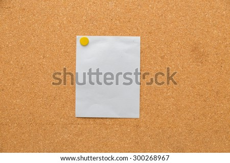 cork board with yellow sticky note pinned