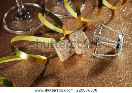 Cork from champagne bottle and two glasses on golden background - stock photo