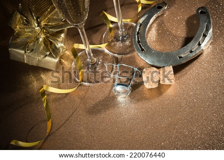 Cork from champagne bottle with a horseshoe in front of two glasses and streamers - stock photo