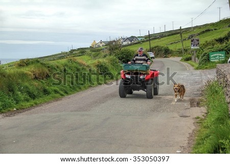 CORK, IRELAND - JUNE, 6 2012: A man with his loyal dog taking leisure time sightseeing in rural area of Dingle Penisula, Ireland