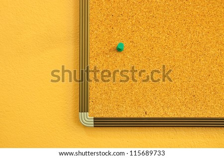 Cork notice board on yellow wall